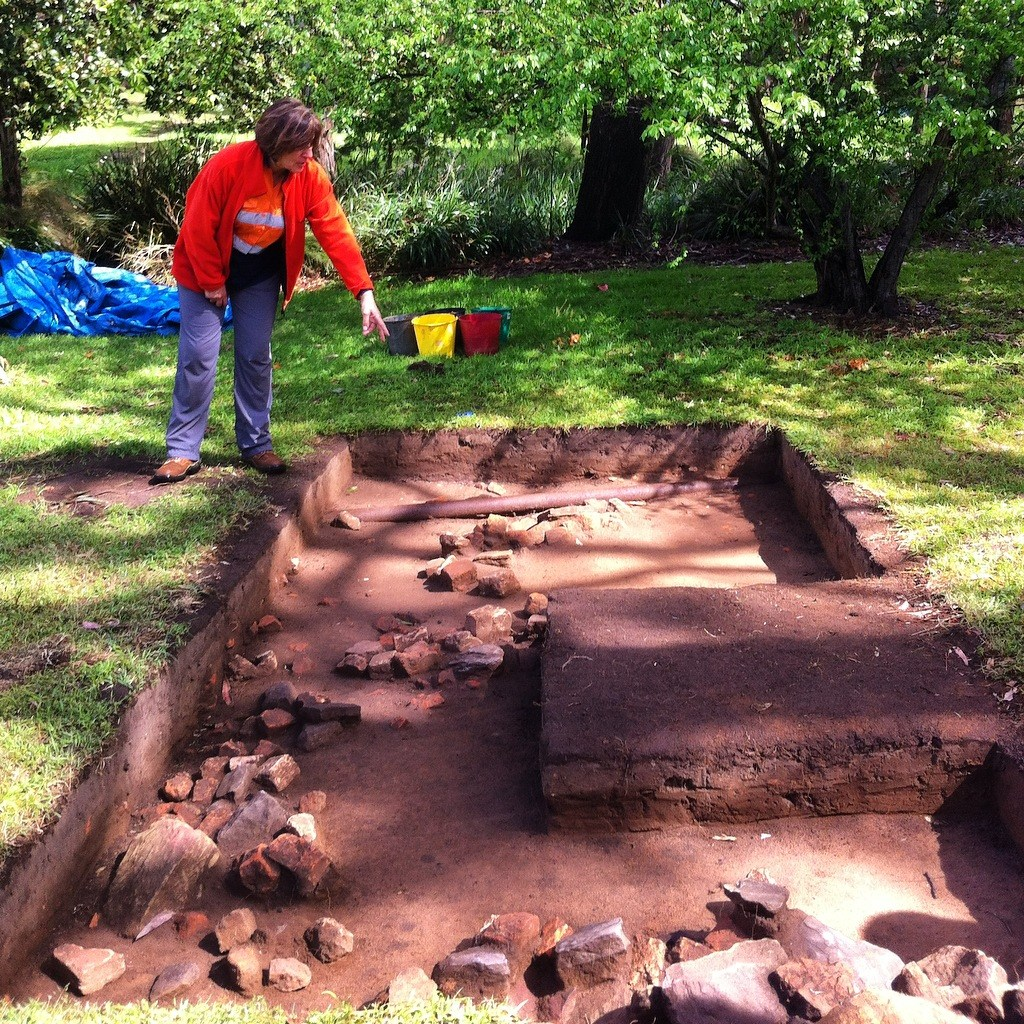 "Archaeologist Anita Yousif talking about the remains of the outer-building discovered behind the 1790s convict hut during excavations carried out by GML Heritage in 2015 at the Murray Gardens, Parramatta Park, formerly part of ""High Street"" [George Street], Parramatta. Photo by Michaela Ann Cameron (2015)."